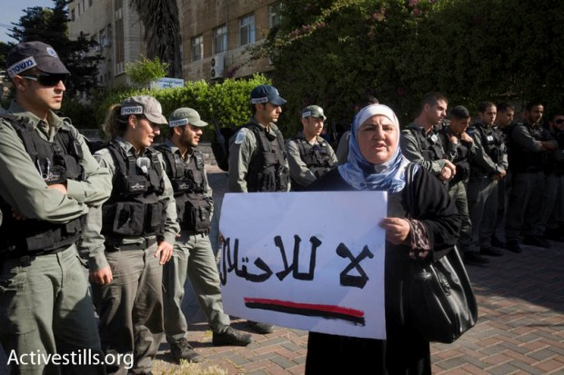 A Palestinian woman in front of policemen in Sheikh Jarrah, April 23 2010 (photo: Oren Ziv/ Activestills.org)