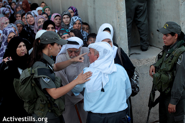 An Israeli border policewoman turns an elderly Palestinian away as thousands of Palestinians try to make their way to Bethlehem checkpoint into Jerusalem to attend the Ramadan Friday Prayers in the Al-Aqsa Mosque, August 10, 2012. (Photo: Anne Paq/Activestills.org)