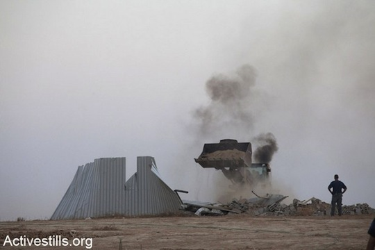 A bulldozer of the Israeli Land Administration tears down a house during the third demolition of Al-Araqib in August 2010.