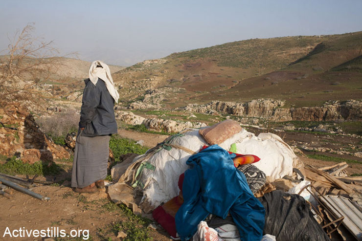 A member of Sariya family stands next to his family belongings in the village of Al-Mayta following a demolition in the Jordan Valley, Area C. (Photo by Activestills.org)