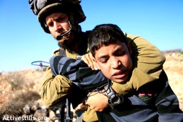 Sodier arresting child in Beit Omar, 2010 (Anne Paq / Activestills)