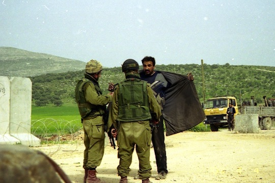 Israeli soldiers search a Palestinian at an IDF checkpoint. (photo: Breaking the Silence)