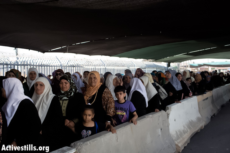 Palestinian women wait to cross from Qalandiya checkpoint outside Ramallah, West Bank, into Jerusalem to attend the Ramadan Friday Prayers in the Al-Aqsa Mosque, July 19, 2013. (Photo by: Oren Ziv/ Activestills.org)