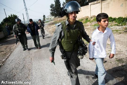 Israeli Border Police officer detains a Palestinian child at a protest in Kufr Qaddum, January 25, 2013. (Yotam Ronen/Activestills.org)