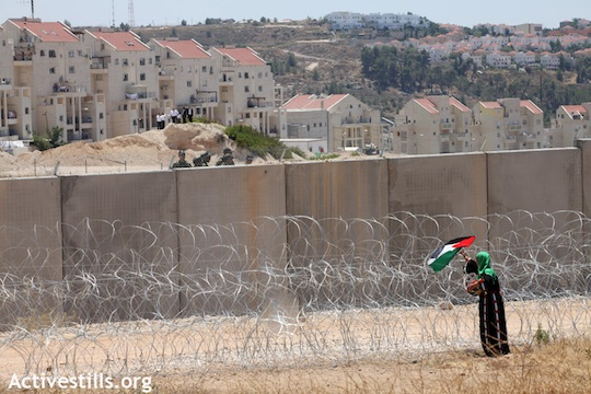 Illustrative photo: An activist puts a Palestinan flag on the Separation Wall facing the Modi'in Illit settlement (Photo: Anne Paq/ Activestills.org)