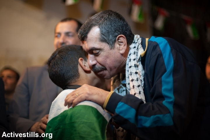 Freed Palestinian prisoner Khaled Al-Azraq greets a young family member in their home in Aida Refugee Camp, West Bank, October 30, 2013. (Ryan Rodrick Beiler/Activestills.org)