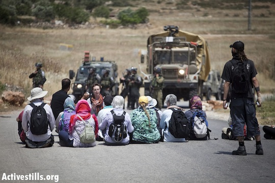 "Demonstrators sit in front of the ""Skunk"" water canon, during the weekly protest against the occupation in the West Bank village of Nabi Saleh, May 18, 2012. (Photo by: Oren Ziv/ Activestills.org)"