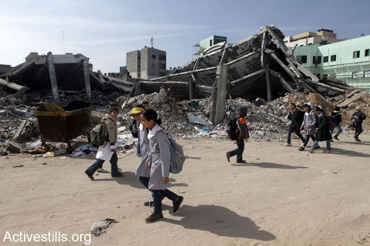 Palestinian children walking by demolished buildings of the Civil department of the Interior Ministry heavily bombed during last November's Israeli assault against the Gaza Strip, February 10, 2013.
