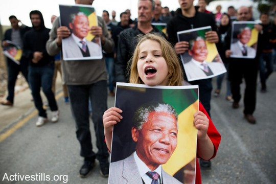A protester holding a poster with Nelson Mandela's portrait, during a demonstration in the West Bank village of Nabi Saleh, December 7, 2013. The demonstration marked four years of the popular struggle in Nabi Saleh, while commemorating the killing of Mustafa Tamimi and Rushdi Tamimi by Israeli army forces, and 26 years since the First Intifada (photo: Activestills)