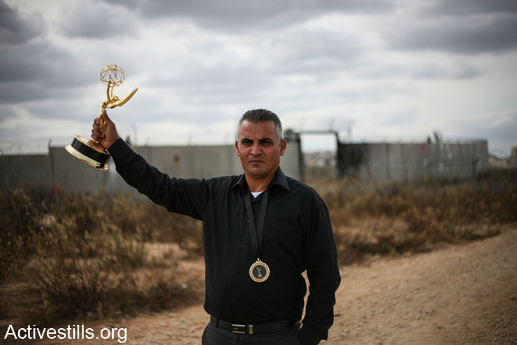 Five broken cameras director and Emmy Award winner, Emad Burnat, holds his award in front of the Israeli wall, during the weekly demo against the wall and occupation in the West Bank village of Bi'lin, Novmber 29,2013. The village celebrated return of Burnat to Bil'in in today's weekly demonstration.