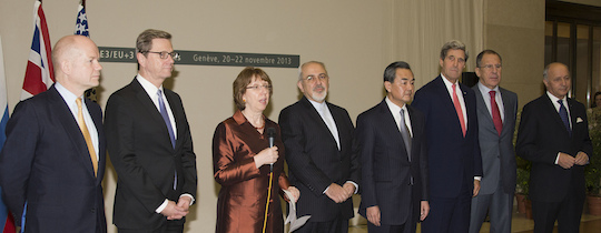 U.S. Secretary of State John Kerry and his fellow P5+1 foreign ministers, as well as Iranian Foreign Minister Javad Zarif, center, listen as European Union High Representative Catherine Ashton speaks at United Nations Headquarters in Geneva, Switzerland, after the group concluded negotiations about Iran's nuclear capabilities on November 24, 2013. [State Dept.]