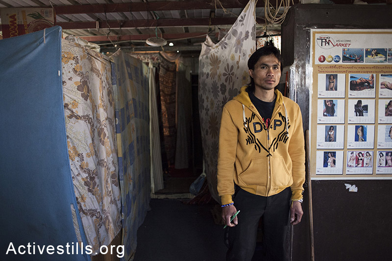 Thongchai Peakuna, an agricultural Thai worker, stands inside a shipping container used as the group's residency, Moshav Yavetz, January 25.1.2014