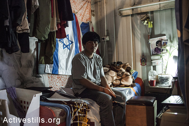 A Thai agriculture worker, sitting on his bed inside a shipping container, used as the group's residency, Moshav Yavetz, January 25.1.2014. (Shiraz Grinbaum/Activestills.org)