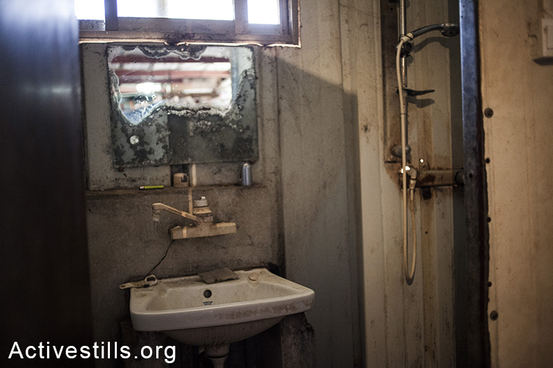 A view on the toilette and shower in the worker's residency, Moshav Yavetz, January 25.1.2014. (Shiraz Grinbaum/Activestills.org)