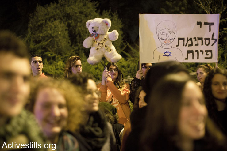 """Students from Ort High School, teachers and supporters take part in a solidarity vigil with the teacher Adam Verete, in Kiryat Tivon, January 25, 2014. Verete is a teacher whose contract is on the line following a complaint from a right-wing student over the """"leftist"""" views he expressed in the classroom. (photo: Oren Ziv/Activestills.org)"""
