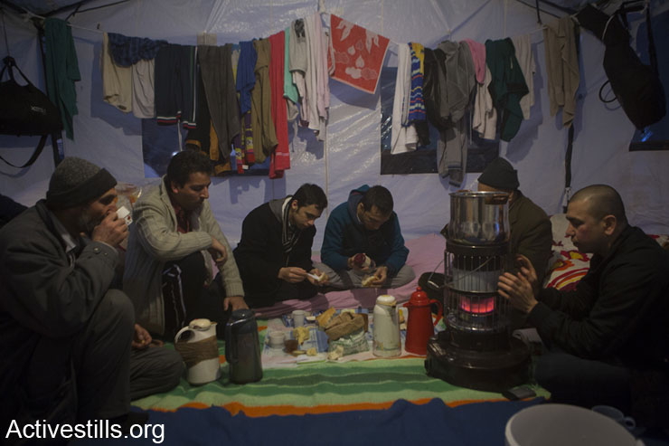 Afghan asylum seekers sharing breakfast in their tent inside the church of the Beguinage used as a temporary shelter in the city center of Brussels, Belgium, January 27, 2014. Belgium has been involved in the Afghan conflict for 10 years. Without papers, Afghan asylum seekers cannot work or find decent housing. They are around 2.7 million Afghans who continue to live in exile and some 450,000 are internally displaced. (photo: Anne Paq/Activestills.org)