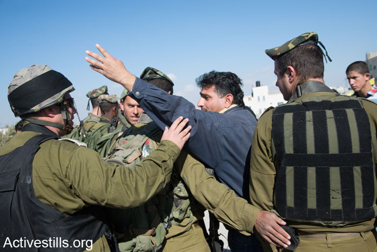 Palestinian activists confront Israeli soldiers during the weekly demonstration against the Israeli separation barrier in the West Bank village of Al Ma'sara, January 17, 2014. The separation barrier would cut off the village from its agricultural lands if it is built as planned. (photo: Ryan Rodrick Beiler/Activestills.org)