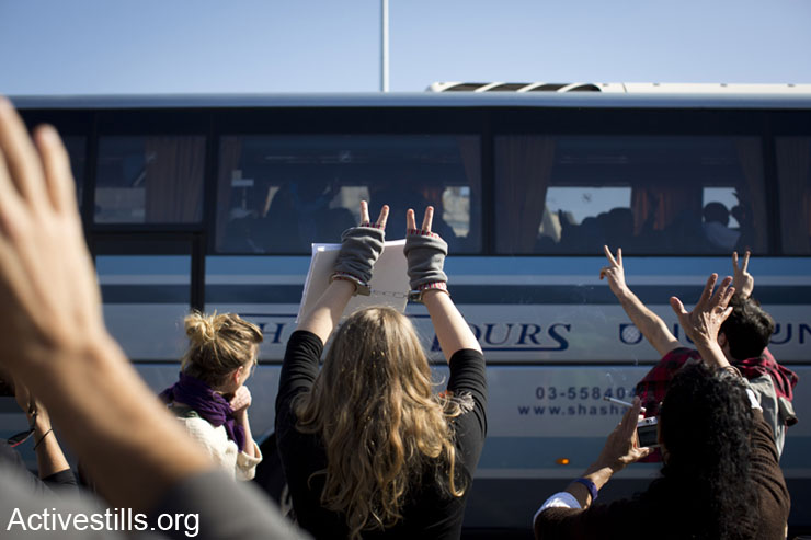 Israeli activists wave as African asylum seekers sit in a bus of the Israeli immigration authority leaving to Holot detention center, Tel Aviv, Israel, January 29, 2014. The Israeli immigration authority summoned  dozens of asylum seekers, ordering them to arrive at Holot detention center. Around 40 arrived. According to human rights organizations, over 1,700 African asylum seekers received similar summons scheduled for the coming weeks, informing them their current visa is cancelled. (photo: Oren Ziv/Activestills.org)