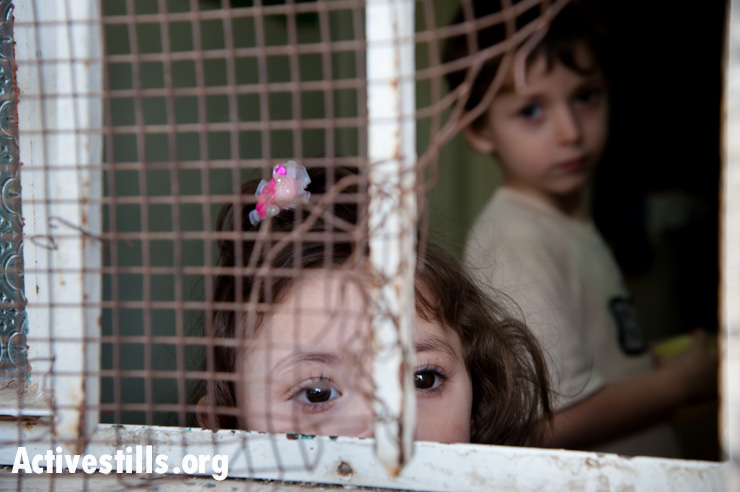 Palestinian children look through a window in their house near the Israeli settlement of Tel Rumeida in the West Bank city of Hebron. Their home has been attacked by settlers on numerous occasions.