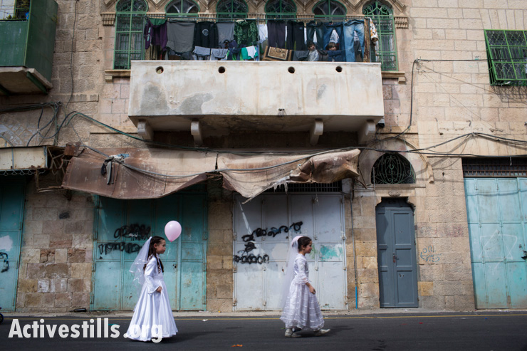 Israeli settler children take part in the traditional Purim holiday parade taking place on Shuhada Street, as Palestinian children, whose access to the street is severely restricted, look from a balcony above, Hebron, West Bank, February 24, 2013.