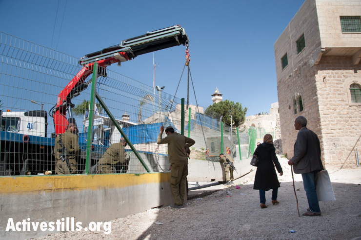 Israeli soldiers place a new concrete and steel barrier to segregate Palestinian pedestrians from Israeli traffic along a road in the H2 section of Hebron, October 22, 2013. The road connects the Ibrahimi Mosque (Tomb of the Patriarchs) in Hebron's old city with the nearby Israeli settletment Kiryat Arba. Israelis are allowed to drive on the road, but Palestinians are prohibited from driving there without special permission, which few are able to obtain.
