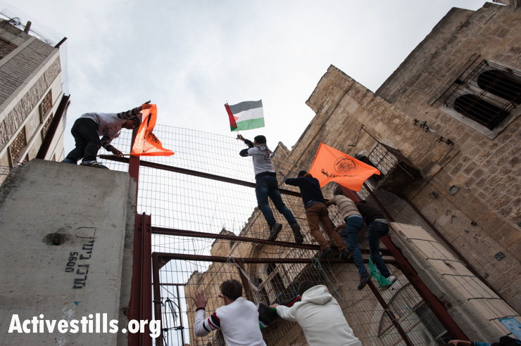 Demonstrators climb a steel and concrete barrier blocking access to Hebron's Shuhada Street during a protest against the closure of the street to Palestinians, February 22, 2013. Hundreds of demonstrators, including foreign and Israeli activists, gathered to mark the 19th anniversary of the massacre by Baruch Goldstein.