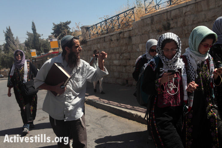 An Israeli settler harasses a group of women activists wearing traditional Palestinian dress who are walking down Shuhada Street as part of an action to protest against the closure of the street to Palestinians in the West Bank city of Hebron, June 13, 2012. The women were stopped after a few meters by the Israeli army and harassed by settlers. Six activists were arrested.