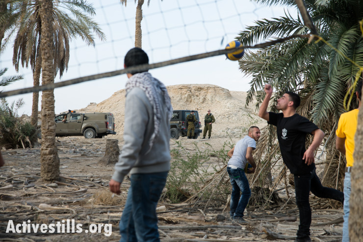 Palestinian activists play volleyball as Israeli soldiers patrol nearby in the Ein Hijleh protest village, in the Jordan Valley, West Bank January 31, 2014. (photo: Activestills.org)