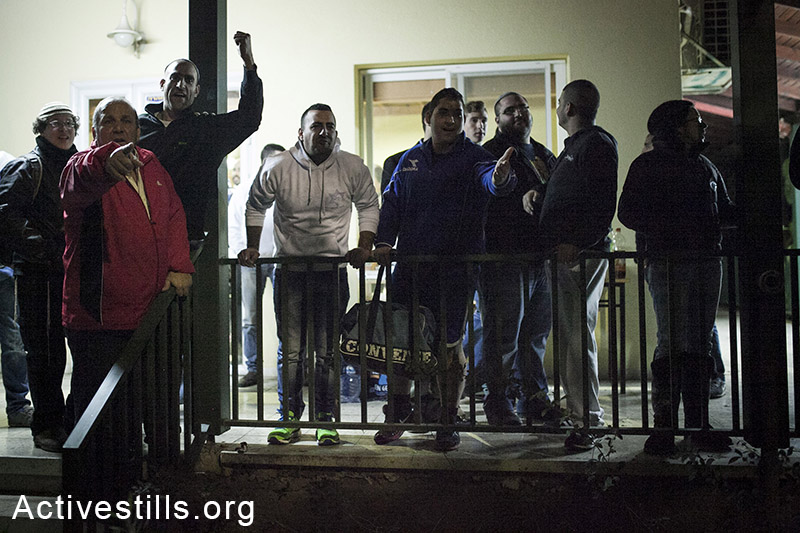 Followers of Michael Ben-Ari shout violent slogans at Kiryat Tivon residents, who protest against an award ceremony for Sapir Sabah, Israeli, February 9, 2014. (Activestills.org)