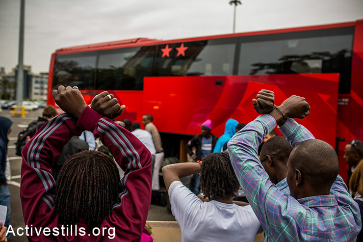 African asylum seekers wait to board a bus of the Israeli immigration authority before leaving for Holot detention center, Tel Aviv, Israel, February 2 , 2014. The Israeli immigration authority summoned several dozen asylum seekers, ordering them to arrive at Holot detention center. Around 40 complied. According to human rights organizations, over 1,700 African asylum seekers received similar summons scheduled for the coming weeks, informing them that their current visa is cancelled. (photo: Yotam Ronen/Activestills.org)