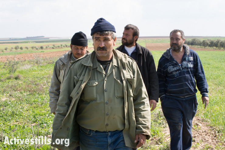 Palestinian farmers walk through fields near Gaza's eastern border with Israel, Al Montar, February 17, 2014. Sami Harazin (second from the right) was shot in the leg six years ago by the Israeli military as he worked in his land and has lost 11 dunums of land to the no-go zone. (photo: Ryan Rodrick Beiler/Activestills.org)