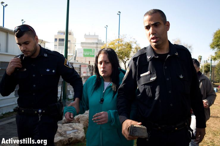 An Israeli policeman (right) holds a stone he took from a right-wing protester (center) after she tried to attack two neighbors. The woman was not detained or questioned by the police.