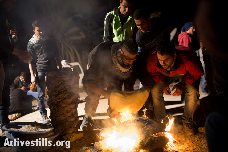 Palestinian activists bake flatbread over an open fire in Ein Hijleh protest village, January 31, 2014. (photo: Activestills.org)