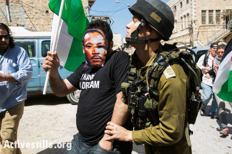 A demonstrator wearing a Martin Luther King Jr. mask is arrested on Shuhada Street by an Israeli soldier during a demonstration against the planned visit of U.S. President Barak Obama to the West Bank, Hebron, March 20, 2013.
