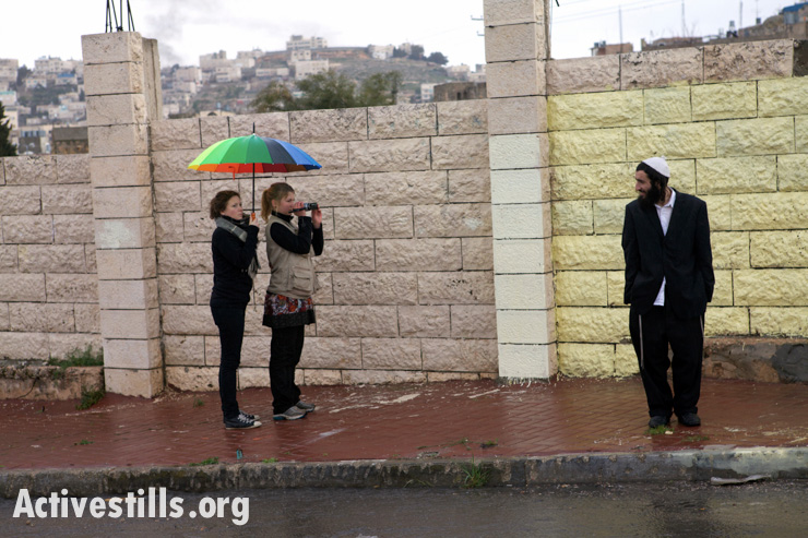 International observers film a settler during a protest calling for the opening of Shuhada Street, in Hebron, February 25, 2010. Activists with various international human rights organizations provide protective presence by accompanying Palestinians who face violence from settlers and soldiers.