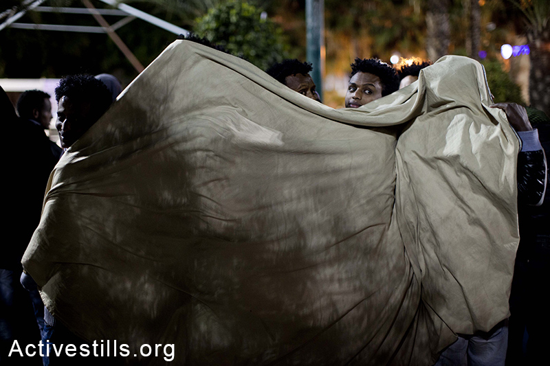 African asylum seekers try to warm together on the second night of a sit-in at Levinsky park in Tel Aviv, protesting against the new detention center, calling to the Israeli government to recognize their refugee rights, February 3, 2014. (Activestills.org)