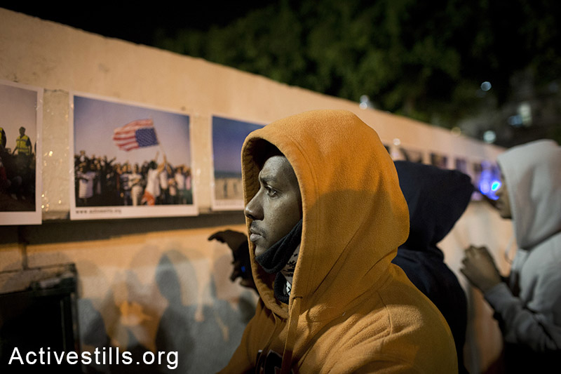African asylum seekers watch an Activestills photo exhibit on the second night of a sit-in at Levinsky park in Tel Aviv, February 3, 2014. (Activestills.org)