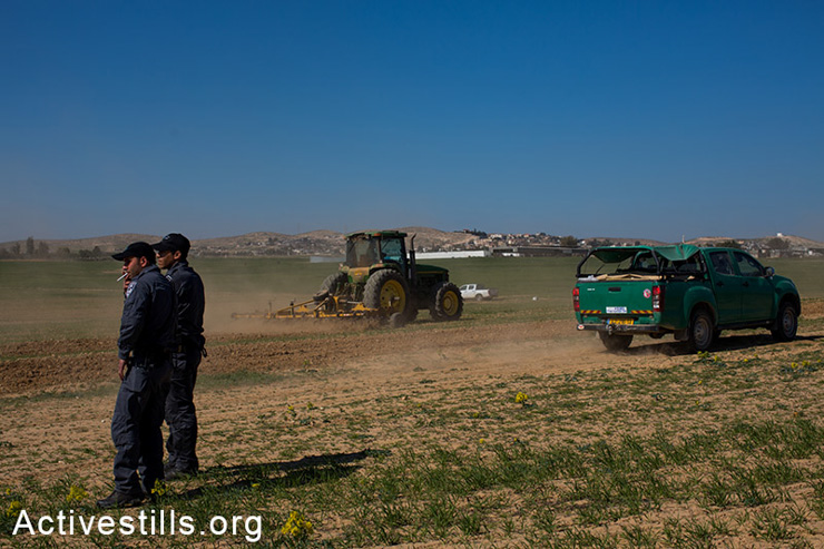 Israeli police guard tractors plowing Bedouin wheat fields off-season, Negev, Israel, February 5, 2014. Israeli authorities plow Bedouin fields every year at this time in order to prevent the owners of the land from making agricultural use of it. (photo: Yotam Ronen/Activestills.org)