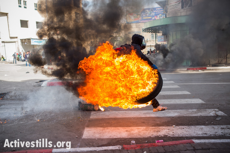 A Palestinian youth rolls a burning tire during a protest against the closure of the Shuhada Street to Palestinians in the West Bank city of Hebron February 21, 2014. Some 500 protesters, including foreign and Israeli activists, gathered to mark the 20th anniversary of the closure of the street.