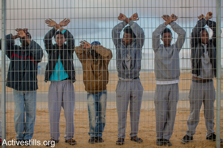 African asylum seekers jailed in Holot detention center protest behind the prison's fence, as other asylum seekers take part in a protest outside the facility, in Israel's southern Negev desert, February 17, 2014.