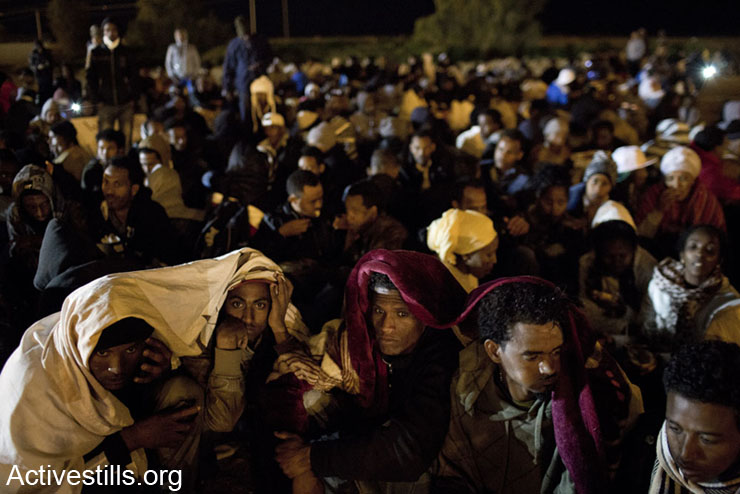 African asylum seekers sit on the ground after taking part in a protest outside the Holot detention center, in Israel's southern Negev desert, February 17, 2014.