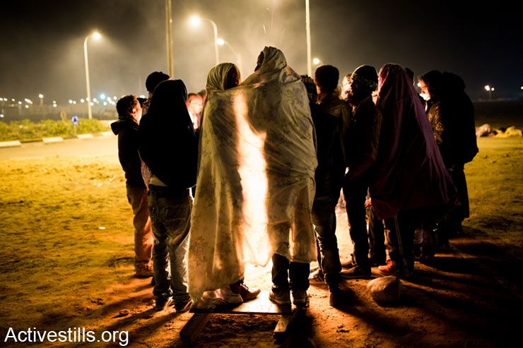 African asylum seekers gather around a fire after taking part in a protest outside the Holot detention center, in Israel's southern Negev desert, February 17, 2014.