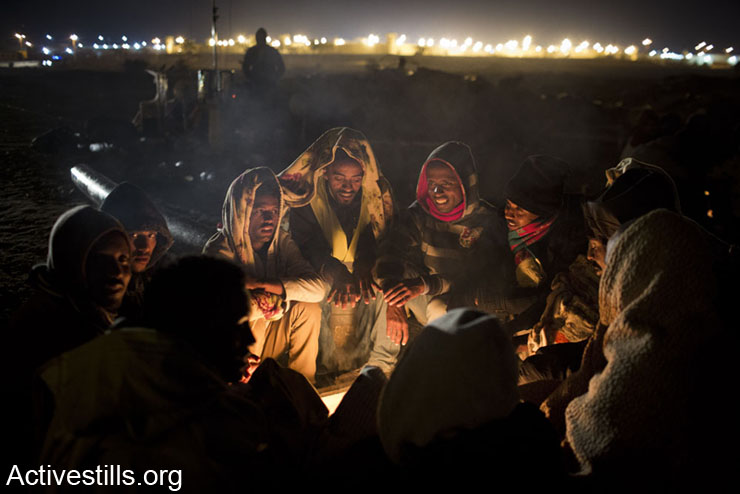 African asylum seekers gather around the fire in the early morning of a second day of protest outside the Holot detention center where hundreds of Aylum seekers are jailed, February 18, 2014 in the southern Negev desert of Israel.