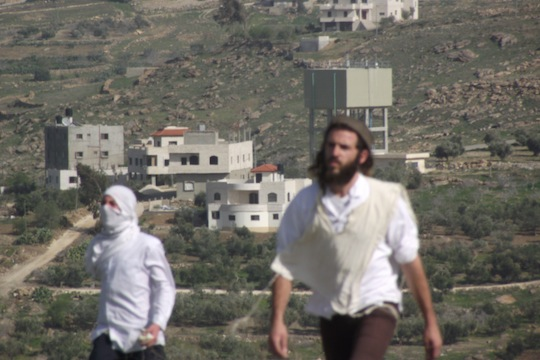 Settlers from Havat Gilad throw stones at Palestinian homes in the nearby village of Jit. (photo courtesy of Rabbis for Human Rights)