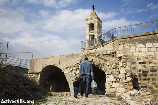 The Palestinian village of Biram, Israel, December 29, 2012. Descendants of the original residents of the Palestinian village of Biram walk through an archway of what was once the destroyed village's church. Today, the site has been declared as a national park. Residents of the village were forced out by the Israeli army in 1949 and have not been allowed to return since, despite a 1951 High Court decision upholding their right to do so. (Photo by Oren Ziv/Activestills.org)
