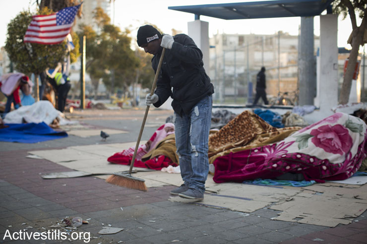 An Eritrean Asylum seeker cleans, after spending the night in Levnisky park, South Tel Aviv, on their eighth day of an on going protest, on the early hours of February 9, 2014. (photo: Oren Ziv/Activestills.org)