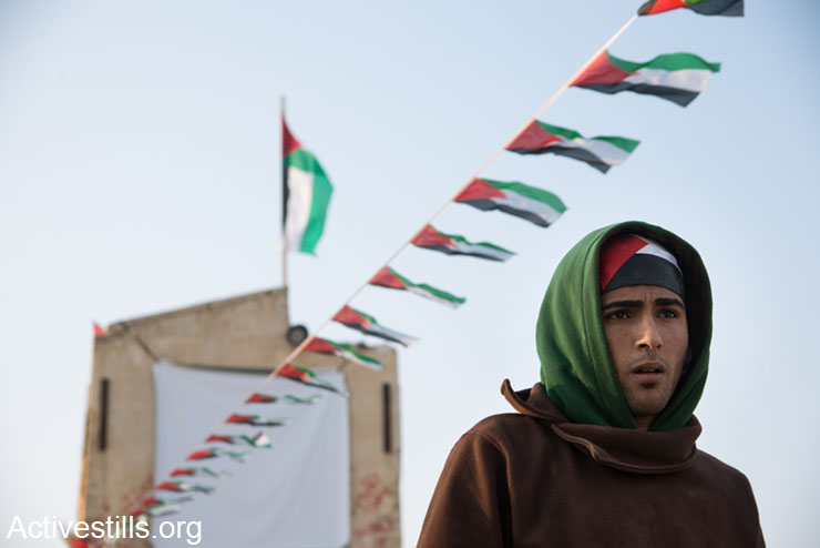 A Palestinian youth stands among the buildings of the Jordan Valley protest village of Ein Hijleh, West Bank, February 6, 2014. As part of its Melh Al-Ard (Salt of the Earth) campaign, the Palestinian Popular Struggle Coordination Committee began on Friday January 31 to restore and occupy abandoned homes in Ein Hijleh to protest the ongoing Israeli annexation of the Jordan Valley. (photo: Ryan Rodrick Beiler/Activestills.org)