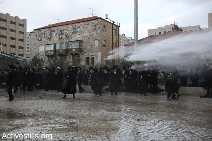 Ultra-orthodox Jews take cover as an Israeli police water canon sprays the crowd under the Chord Bridge at the entrance to West Jerusalem during a protest against drafting ultra-orthodox Jews into the Israeli military, February 6, 2014. Several thousand ultra-orthodox Jews protested in Jerusalem and other cities and towns after an ultra-orthodox  young man was arrested when he dodged the draft. Police used water canon, horses and physical force to break up the protest. (photo: Tali Mayer/Activestills.org)
