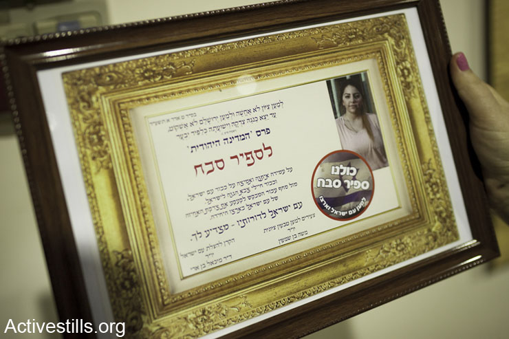 "The ""Jewish State Award"" is given to Sapir Sabah, during a ceremony orgenized by Michael Ben-Ari, Israel, February 9, 2014. Sapir Sabah is a high-school student who publicly denounced her teacher, Adam Verete, for questioning the morality of the Israeli army's actions in class. The award ceremony was attended by Itamar Ben-Gvir, Baruch Marzel and their followers. (photo: Activestills.org)"