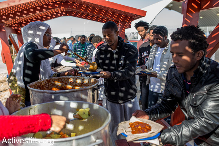 African asylum seekers held in the Holot detention center eat food brought by community members during a solidarity visit held outside the detention center, Negev, February 8, 2014. (photo: Activestills.org)